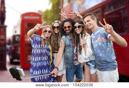 summer holidays, travel, technology and people concept - smiling young hippie friends taking picture by smartphone on selfie stick and showing peace gesture over london city street background