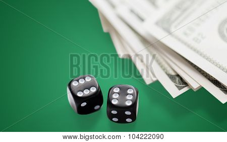 casino, gambling and fortune concept - close up of black dice and dollar cash money on green table background