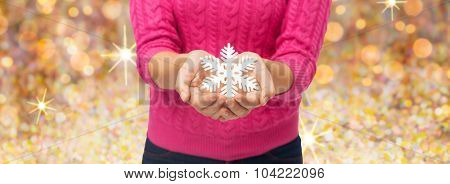 christmas, winter, holidays and people concept - close up of woman in pink sweater holding snowflake over golden lights background