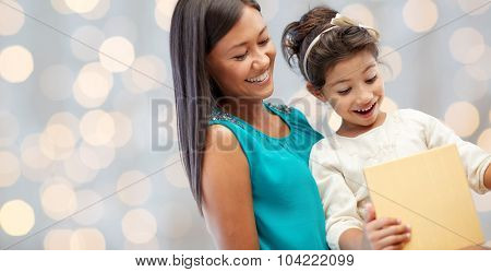 holidays, birthday, family, childhood and people concept - happy mother and little girl with gift over lights background