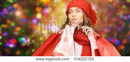 winter holidays, christmas, sale and people concept - young woman in red hat and scarf carrying shopping bags over lights background