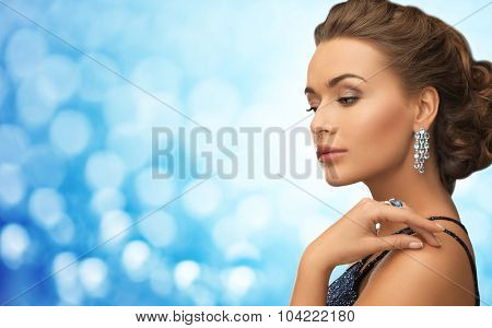 people, holidays, jewelry, luxury and glamour concept - beautiful woman with beautiful diamond earrings over blue lights background