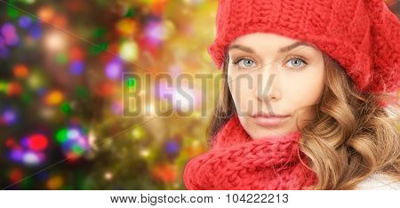 winter, christmas and people concept - young woman in red hat and scarf over holidays lights background