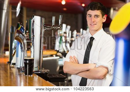 Portrait of confident male bartender at bar counter