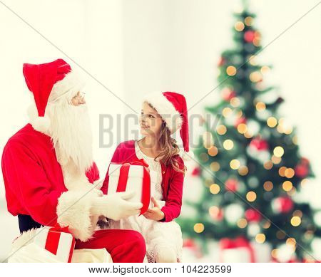 holidays, childhood and people concept - smiling little girl with santa claus and gifts over christmas tree lights lights background