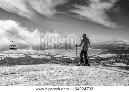 Skier stay on the peak of mountain in sunny day.