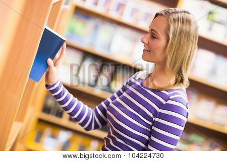 Young woman selecting book from bookshelf in library