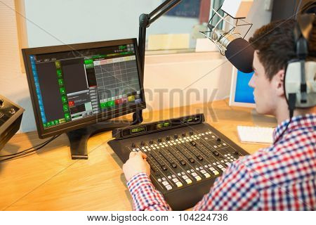 High angle view of radio host operating sound mixer while looking in monitor at studio