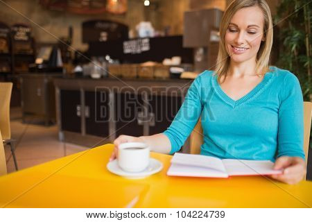 Young woman holding book with coffee cup on table at cafe