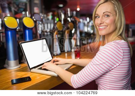 Portrait of happy woman using laptop at bar counter