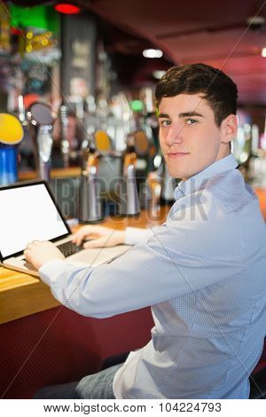 Portrait of confident man using laptop at table in bar
