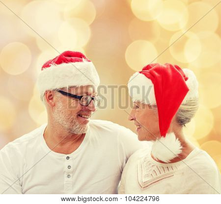 family, holidays, christmas, age and people concept - happy senior couple in santa helper hats sitting on sofa over beige lights background