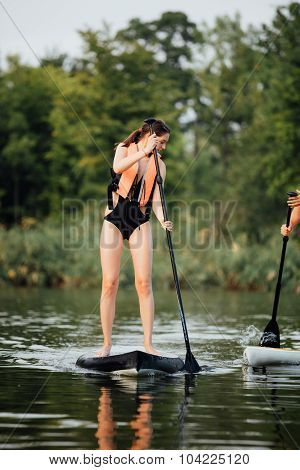 Woman Doing Stand Up Paddle On A Lake Surrounded By Trees