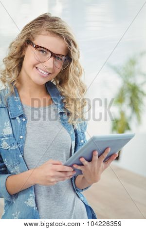 Portrait of happy woman wearing eyeglasses while using digital tablet at office