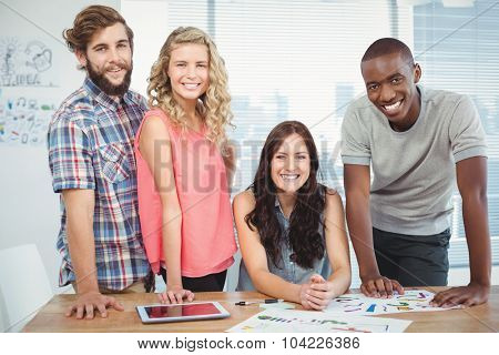 Portrait of happy woman with coworkers at desk in office