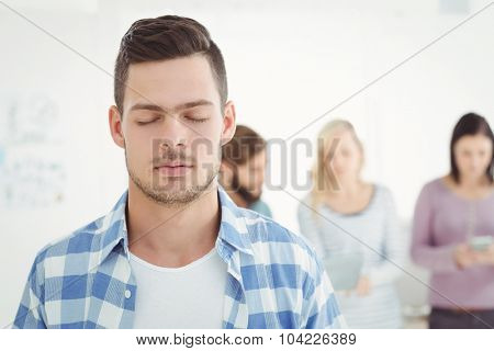 Man with eyes closed while standing at office