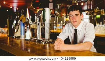 Portrait of confident male bartender sitting at bar counter