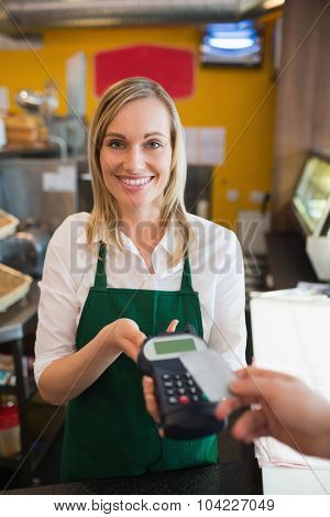 Portrait of female worker accepting payment from customer through credit card in bakery
