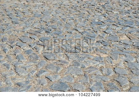 Old cobblestone road paved with urban stones