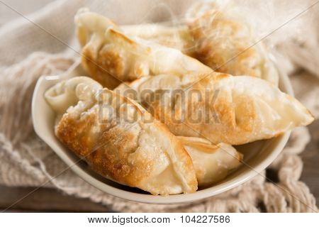 Close up fresh pan fried dumplings on bowl with hot steams. Asian gourmet on rustic vintage wooden background.