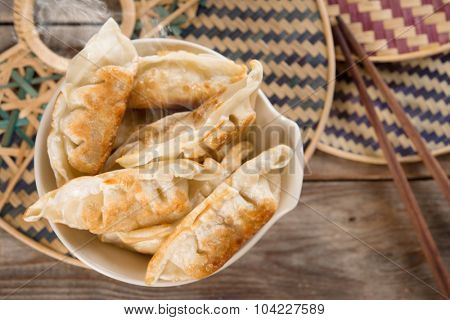 Top view fresh pan fried dumplings on bowl with hot steams. Asian gourmet on rustic vintage wooden background.