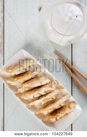 Top view fresh pan fried dumplings on plate with hot steams. Asian cuisine on rustic vintage wooden background.