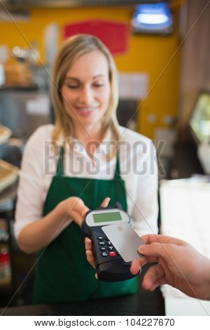 Female worker accepting payment from customer through credit card in bakery