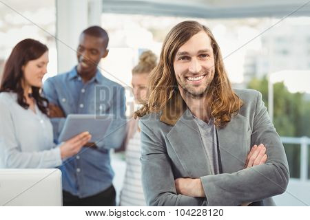 Portrait of smiling man with arms crossed while coworkers discussing at office