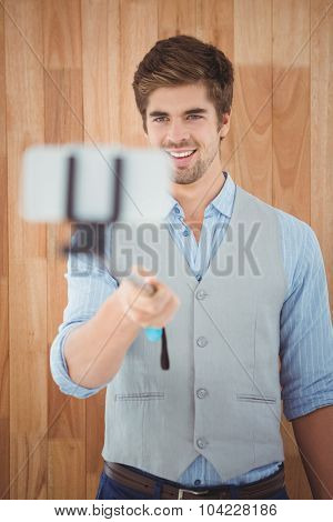 Businessman smiling while taking selfie against wooden wall in office