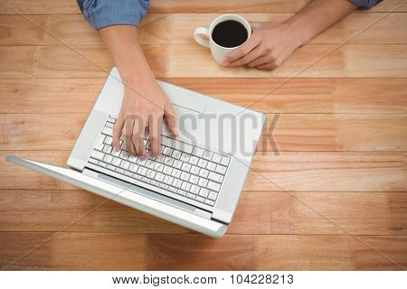 Man holding coffee while working on laptop at desk in office