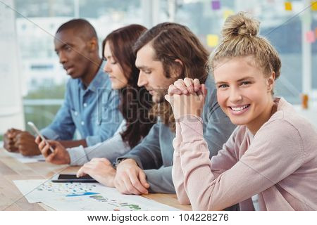 Portrait of smiling woman with hands clasped while sitting at desk with coworkers in office