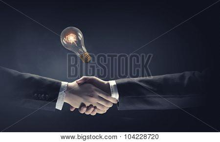 Business partners handshake and glowing light bulb