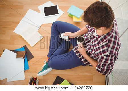 High angle view of hipster using smartphone while holding black coffee in office
