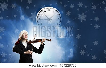 Woman in formal suit and Santa hat playing violin