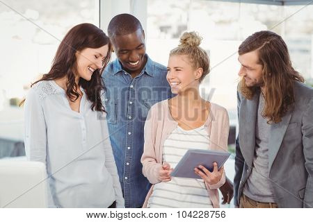 Smiling woman holding digital tablet and discussing with coworkers at office
