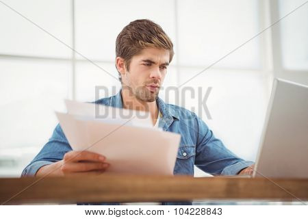 Low angle view of hipster holding documents while working on laptop in office