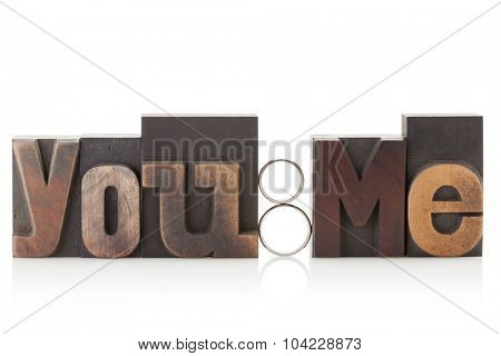 You & me, phrase written with printing blocks and wedding rings