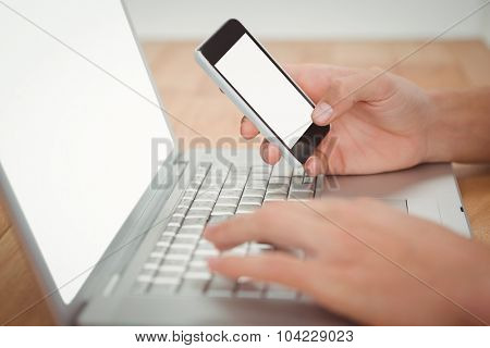 Cropped hand of man holding mobile phone while typing on laptop at desk in office