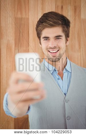 Happy businessman taking selfie while standing against wooden wall