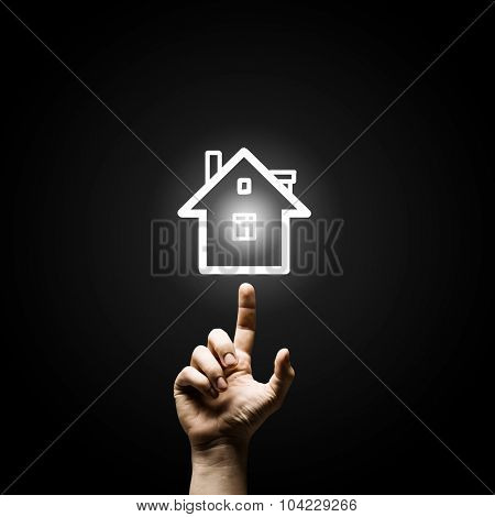 Close up of man hand pointing with finger at house model
