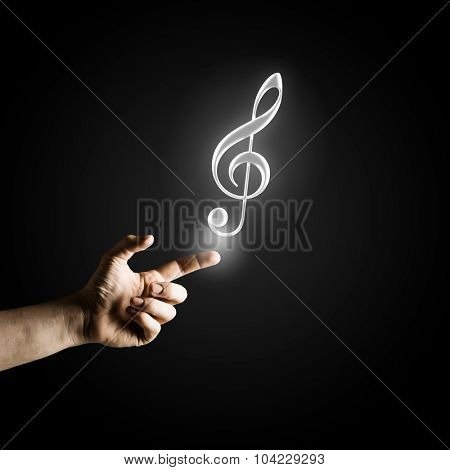 Male hand pointing with finger at music sign