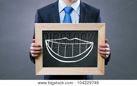 Unrecognizable businessman holding chalkboard with drawn smilie