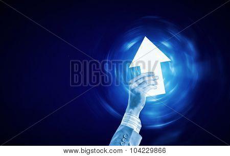 Businessman hand with digital arrow icon on blue background