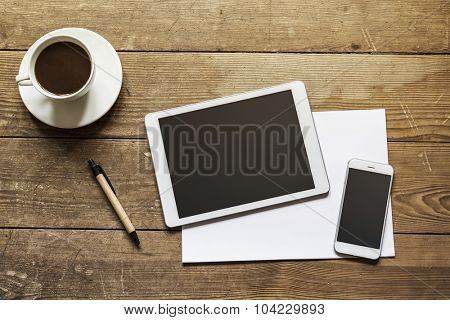 blank tablet and phone over empty white paper on a wooden workspace
