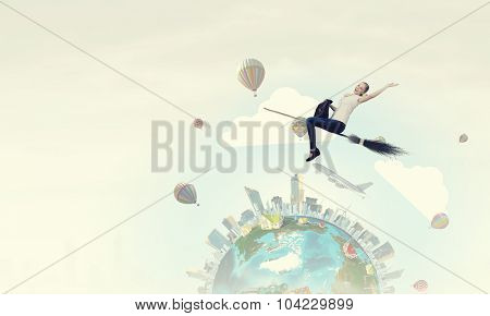 Happy young woman flying in sky on broom. Elements of this image are furnished by NASA