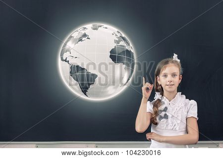 Cute school girl pointing at globe above her head