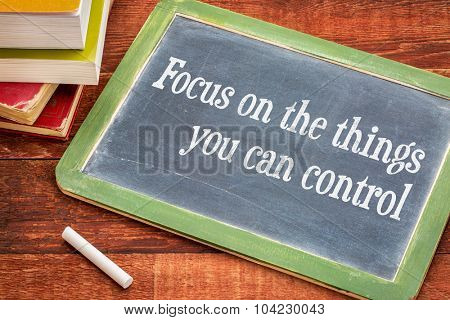 Focus on the things you can control - advice on the slate blackboard with a white chalk and a stack of books against rustic wooden table