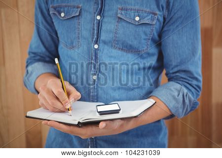Mid section of man writing with pencil on book against wooden wall