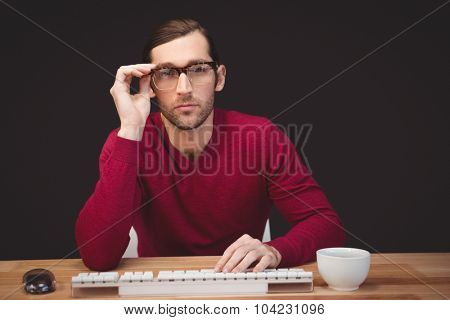 Portrait of confident man wearing eye glasses sitting at desk in office