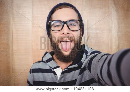 Portrait of happy hipster sticking out tongue against wooden wall